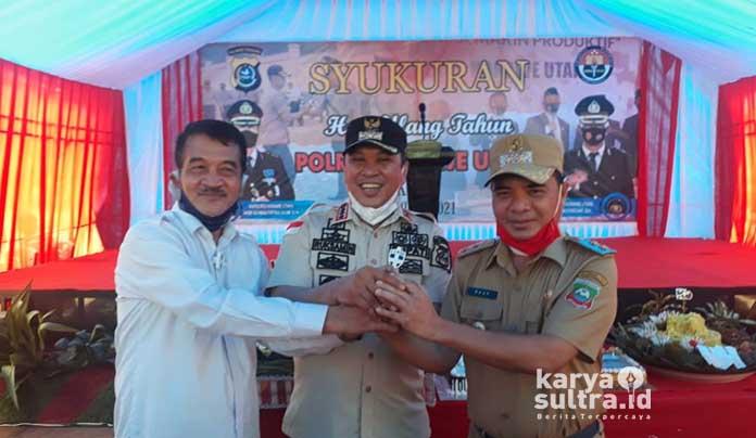 Bupati Konut, Ruksamin bersama Raup dan Abuhaera saling berangkulan tangan di momen syukuran hari jadi Polres Konut.